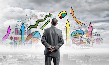 ビジネス戦略のスケッチを見ての実業家の背面図