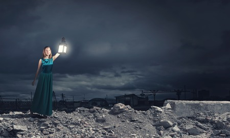 darkness: Young woman in green dress with lantern in darkness