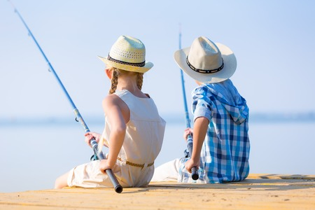 Boy and girl with fishing rods fishing together from a pier photo