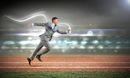 Young businessman in suit running on stadium track