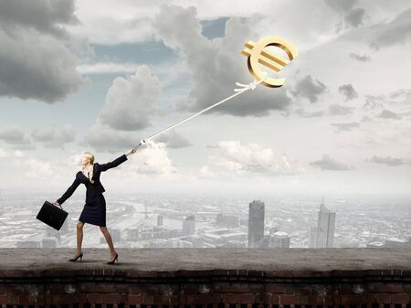pulling money: Young businesswoman pulling euro sign with rope
