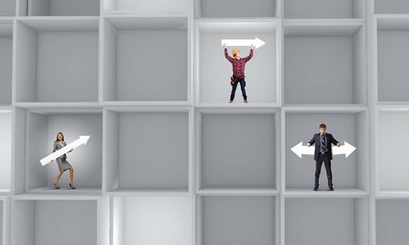 Miniatures of business people standing in cube photo