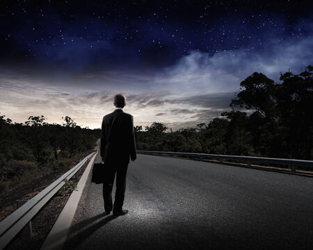 Back view of businessman standing on road and looking far away photo