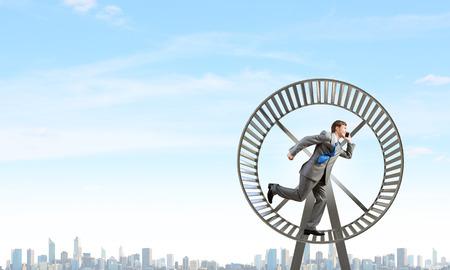 Junger Geschäftsmann in großen Hamsterrad laufen Standard-Bild - 36718519