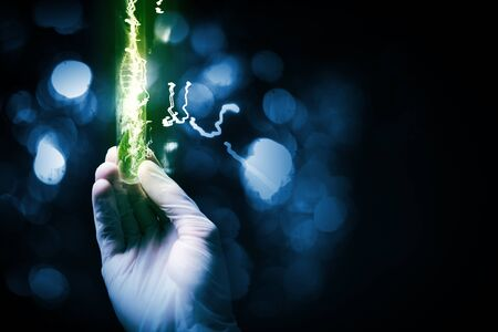 Close up of scientist hand holding tube with leaf