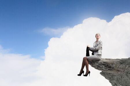 Young businesswoman with suitcase sitting on rock edge