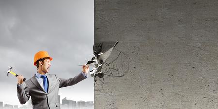 Businessman in helmet hammering nail in brick wall