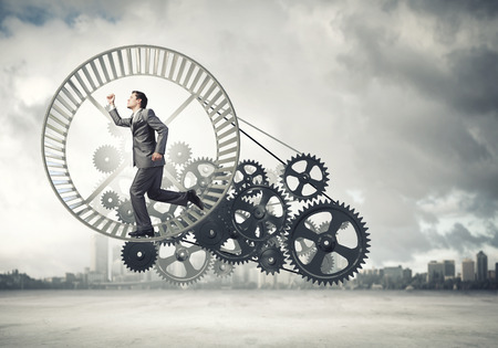 office slave: Young businessman in suit running in hamster wheel Stock Photo