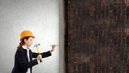 hobnail: Young woman in business suit hitting hobnail with hammer Stock Photo
