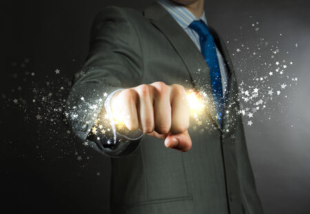 close fist: Close up of businessman grasping star dust in fist