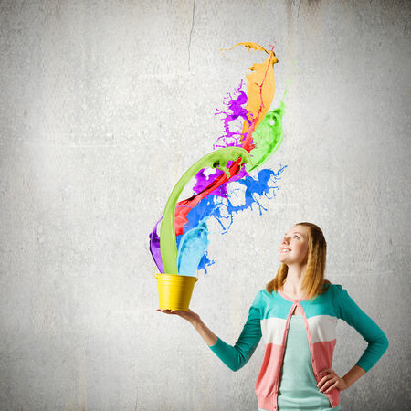 Young woman in casual holding yellow bucket with splashes Archivio Fotografico