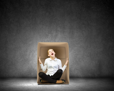 Young businesswoman sitting in carton box and feeling uncomfortable Stock Photo