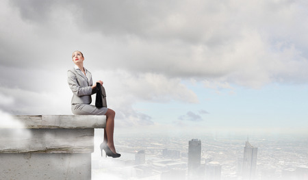 fearless: Fearless businesswoman with suitcase sitting on building top