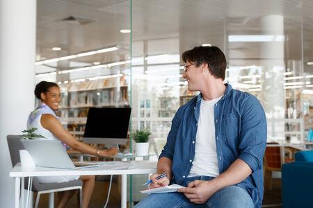 amigas conversando: Tiro de dos colegas que tienen una conversaci�n amable en el mostrador