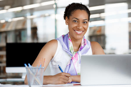 Portrait of a young business woman working on a laptop in a office Stock Photo