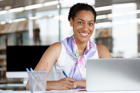 mujer sola: Retrato de una mujer de negocios joven que trabaja en un ordenador port�til en una oficina Foto de archivo