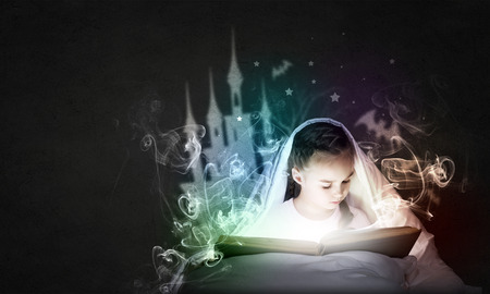 Little cute girl with in bed reading book under blanket Stock fotó