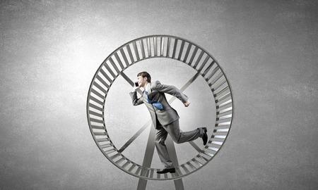 Junger Geschäftsmann in großen Hamsterrad laufen Standard-Bild - 36712094