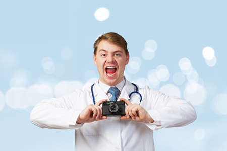 emotionally: Funny young doctor with photo camera screaming emotionally Stock Photo
