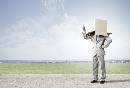 masquerader: Businessman wearing carton box with drawn emotions on head Stock Photo