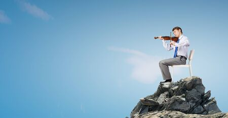 virtuoso: Young businessman sitting in chair and playing violin
