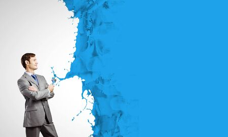 brush in: Young businessman with paint brush in hand