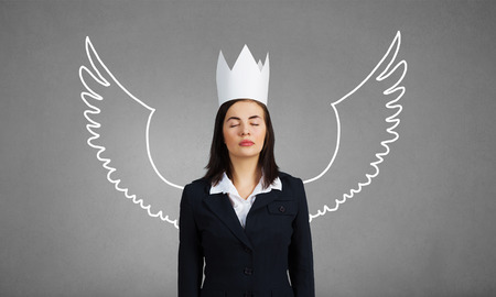 queen of angels: Young businesswoman in crown and with drawn wings behind back