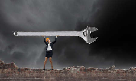 above head: Young businesswoman lifting huge wrench above head Stock Photo