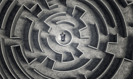 puzzled: Puzzled businessman standing in center of labyrinth