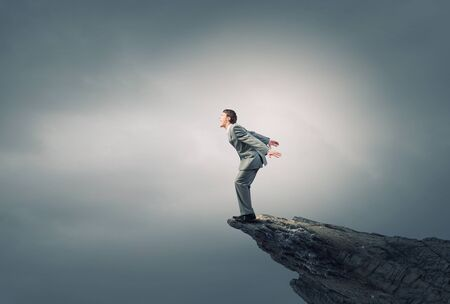 edge of cliff: Determined businessman jumping in deep from edge of cliff