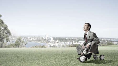 wheeled: Young handsome businessman riding three wheeled bicycle Stock Photo