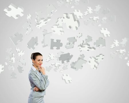 Portrait of pretty young businesswoman and many puzzle elements around Stock Photo