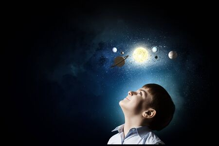 universe: Cute boy of school age exploring space system Stock Photo