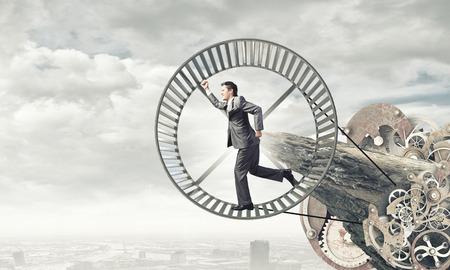 Junger Geschäftsmann in der Klage im Hamsterrad laufen Standard-Bild - 36902010