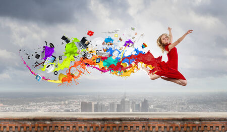 Young woman dancer in red dress jumping high photo