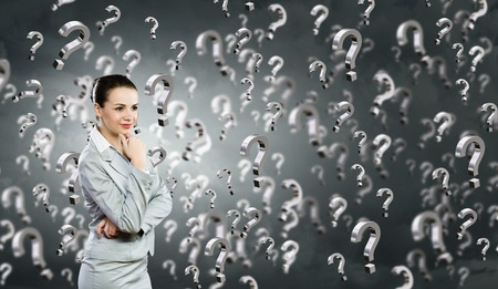 decision making: Portrait of pretty young businesswoman and many question marks around Stock Photo