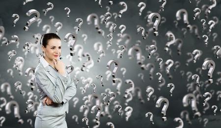 toma de decisiones: Retrato de bastante joven empresaria y muchos signos de interrogación alrededor