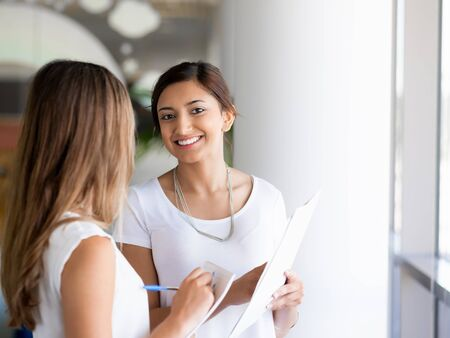 next to each other: Two female collegues standing next to each other in an office