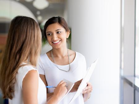 dos personas hablando: Dos colegas mujeres de pie junto a la otra en una oficina