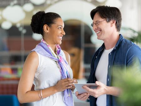 personas platicando: Dos colegas de pie junto a la otra en una oficina