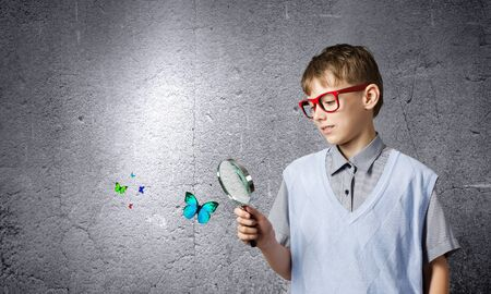investigating: School boy examining butterfly with magnifying glass Stock Photo