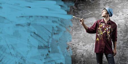 pintor: Pintor joven hombre guapo con pincel en mano
