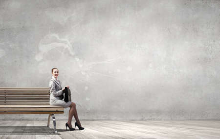 busineswoman: Young businesswoman with suitcase sitting on bench