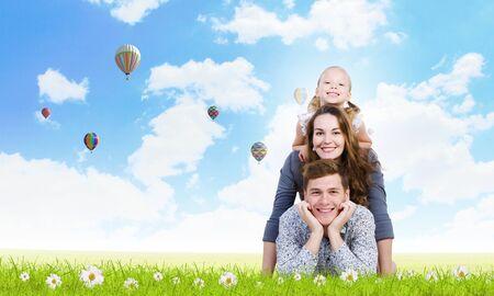 Happy family of three lying on green grass