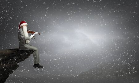 Businessman in Santa hat and beard playing violin Stock Photo