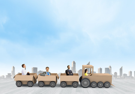 Business people riding carton train. Teamwork concept photo