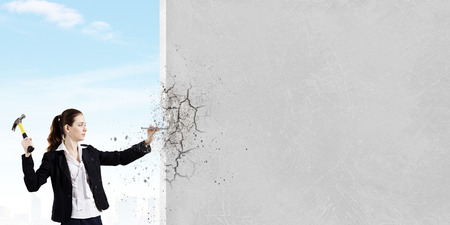 tradeswoman: Young woman in business suit hitting hobnail with hammer Stock Photo