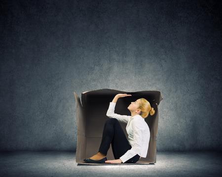 ダン ボール箱に座っていると、不快感の若い実業家 写真素材