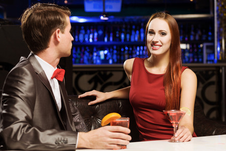 accompanied: Young handsome man in bar accompanied by elegant lady