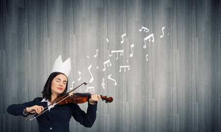 Young pretty businesswoman in paper crown playing violin